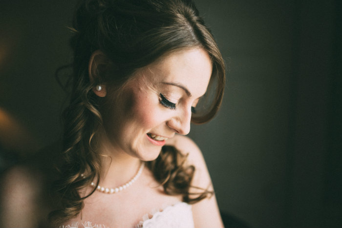 A close up of the beautiful Bride, Soft makeup and false eyelashes give the perfect fan of lashes.
